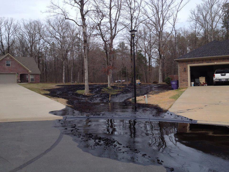 PHoto of Pegasus tar sand pipeline oil spilling between two homes.